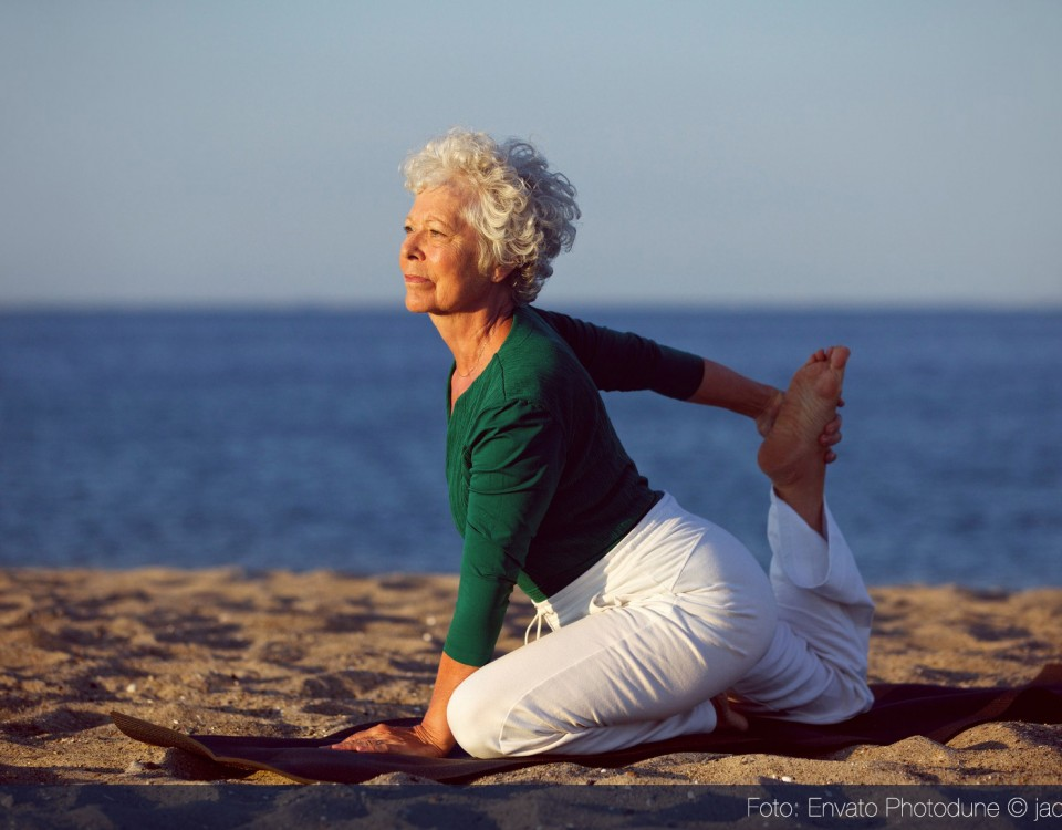 "Ältere Dame beim Yoga, Foto ""Senior woman doing yoga by the ocean"", Lizenz: Photodune @ jacoblund"